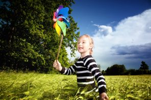young girl running with wind vane in wheat filed